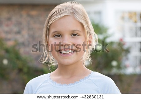 Portrait of a little girl smiling and looking at camera. Young girl enjoying vacation outdoor. Portrait of happy female child with blonde hair girl outside the house. - stock photo