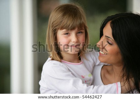 Portrait of a little girl smiling in the arms of a young woman - stock photo