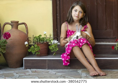 Portrait of a little girl standing on the stairs with rabbit on her lap - stock photo
