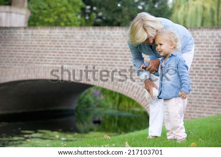 Portrait of a little girl standing outdoors with grandmother in park  - stock photo