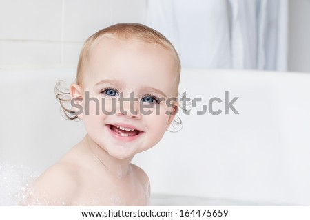 Portrait of a little girl taking a bath - stock photo