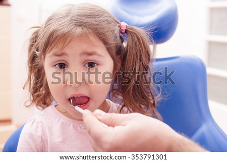 Portrait of a little girl that is sitting with his open mouth and checks the teeth at the dentist - stock photo