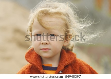 Portrait of a little girl. The wind blows her long thin hair. Shallow DOF. - stock photo
