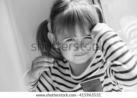 portrait of a little girl upset window ( black and white ) - stock photo