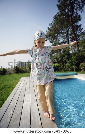 Portrait of a little girl walking beside a pool - stock photo