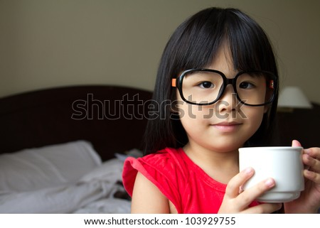 Portrait of a little girl wearing spectacles and hold a cup in hotel room - stock photo