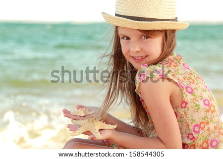 Portrait of a little girl who dreams of a hat on a background of a sea landscape outdoors - stock photo