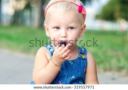 Portrait of a little girl who eats raspberries - stock photo