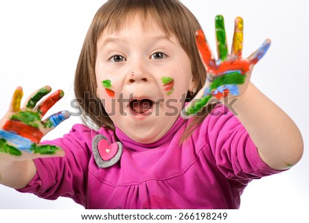 portrait of a little girl who paints bright colored paints. On a white background.