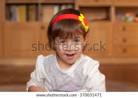 Portrait of a little girl who smiles in the room - stock photo
