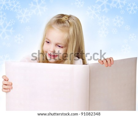 Portrait of a little girl with a book on background with snowflakes - stock photo