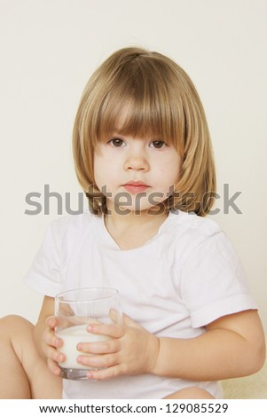 Portrait of a little girl with a cup of milk - stock photo