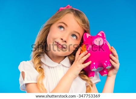 Portrait of a little girl with a pink pig isolated on the blue background