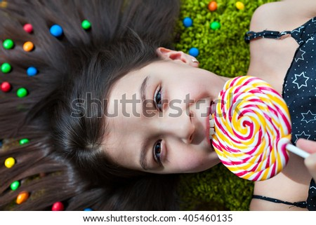 Portrait of a little girl with dark hair lying on the floor among the sweets. Top view of a big yellow and pink lollipop in his mouth. Many candies in her hair. happiness on a child's face. - stock photo