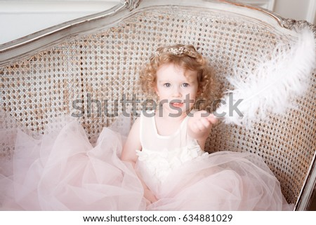 Portrait of a little girl with golden hair with feather