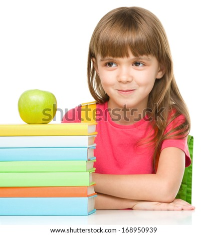 Portrait of a little girl with her books and green apple, isolated over white - stock photo