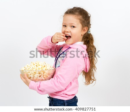 Portrait of a little girl with popcorn isolated on white - stock photo