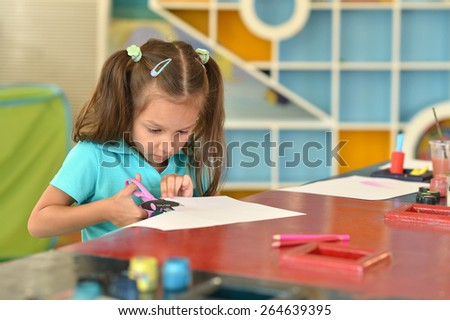 Portrait of a little girl with scissors cuts paper - stock photo
