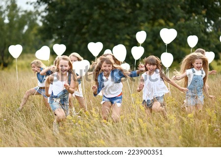 portrait of a little girls in a field with white balloons - stock photo