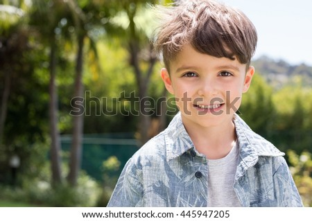 Portrait of a little happy boy looking at camera. Happy kid smiling with toothy smile. Beautiful child in casual outdoor. - stock photo