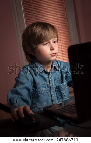 Portrait of a little happy boy using laptop in the living room at home - stock photo
