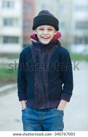 portrait of a little happy homeless boy, poverty, city, street, smiling - stock photo