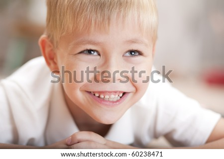 Portrait of a little loughing boy lying on the floor - stock photo