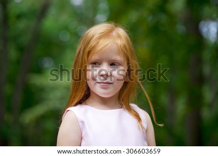 Portrait of a little red-haired girl on the background of summer green forest - stock photo