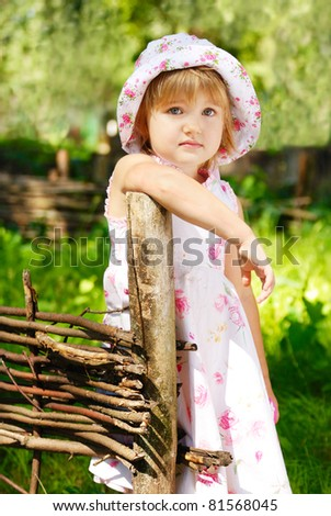 Portrait of a little sad girl standing by fence