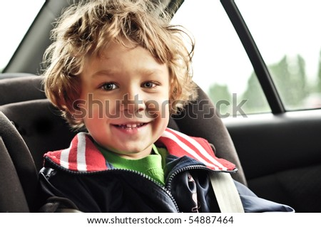 Portrait of a little smiling blond boy in the car - stock photo