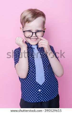 Portrait of a little smiling boy in a funny glasses and tie. School. Preschool. Fashion. Studio portrait over pink background - stock photo
