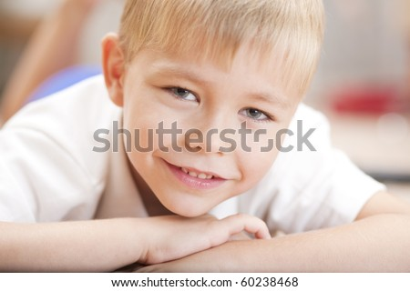 Portrait of a little smiling boy lying on the floor - stock photo