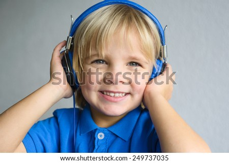 Portrait of a little smiling boy with headphone  - stock photo