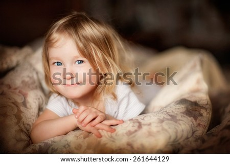portrait of a little smiling girl with tousled blond hair lying on a bed - stock photo