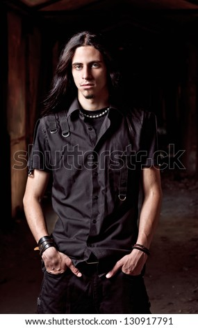 Portrait of a long-haired handsome young man in low key - stock photo