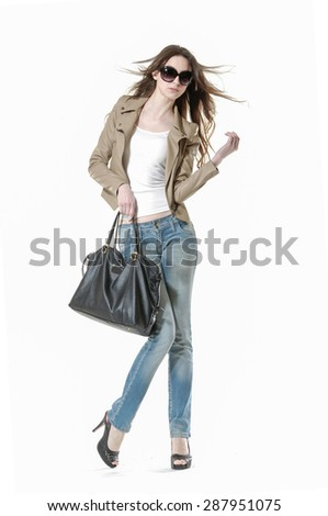 Portrait of a long-haired young woman with bag posing in studo - stock photo