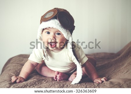 Portrait of a lovable 5 months baby in funny pilot hat, toned image - stock photo
