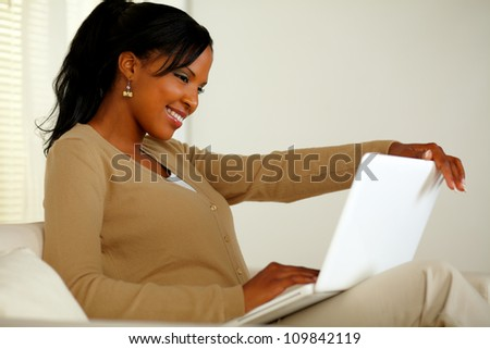 Portrait of a lovely black woman smiling and looking to laptop screen - stock photo