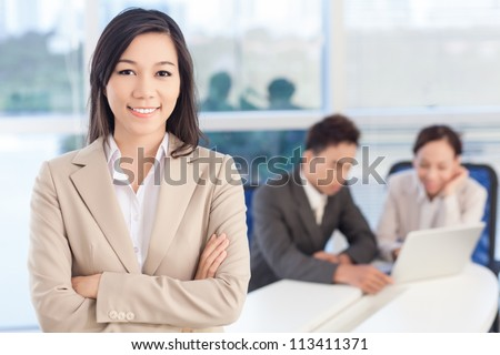 Portrait of a lovely business lady, the embodiment of enthusiasm and success, her colleagues working in the background - stock photo