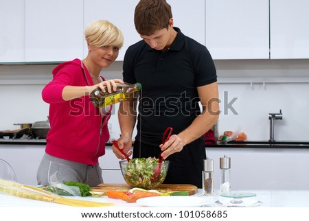 Portrait of a lovely couple making a salad in their kitchen. blond girl and dark haired guy. he mixes salad and she pours olive oil. kitchen is white and filled with light. couple is young and fit  - stock photo