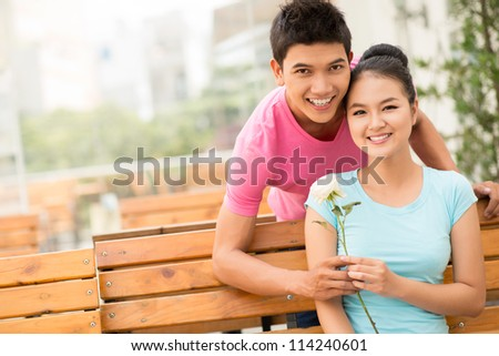 Portrait of a lovely couple on their first date, girl holding a white rose - stock photo
