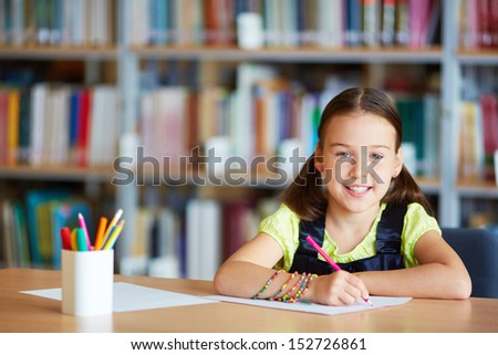Portrait of a lovely girl drawing with pencil in library - stock photo