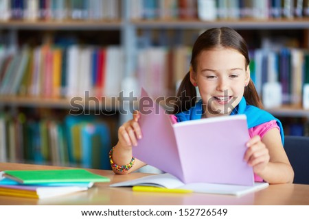 Portrait of a lovely girl reading in library - stock photo