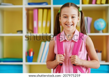 Portrait of a lovely girl with backpack looking at camera - stock photo