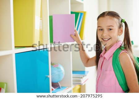 Portrait of a lovely girl with backpack looking at camera in classroom - stock photo