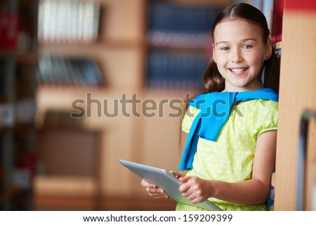 Portrait of a lovely girl with touchpad looking at camera - stock photo