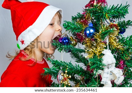 Portrait of a lovely little girl who is wearing Santa hat, she is standing against the Christmas background. - stock photo