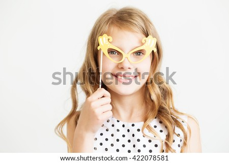 Portrait of a lovely little girl with funny party paper glasses or mask against a white background - stock photo