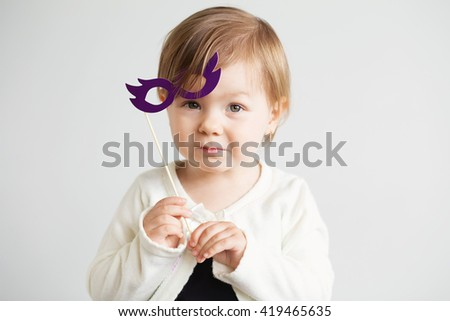 Portrait of a lovely little girl with funny photo props cardboard glasses against a white background. Portrait of a happy little kid in carnival mask - stock photo