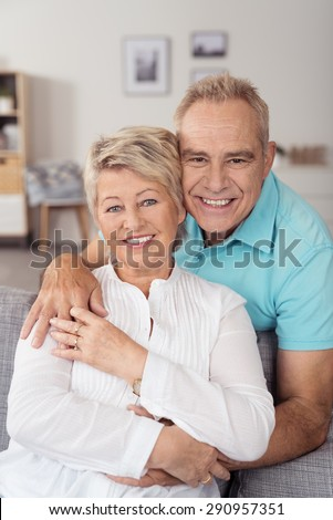 Portrait of a Lovely Middle Aged Husband and Wife at the Living Area, Looking at the Camera with a Toothy Smile. - stock photo